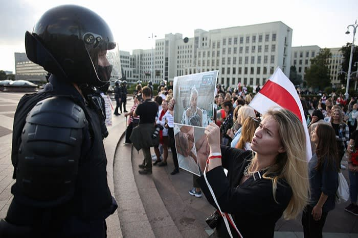 A protester confronts a law enforcement officer at a march disputing the presidential election results in September 2020