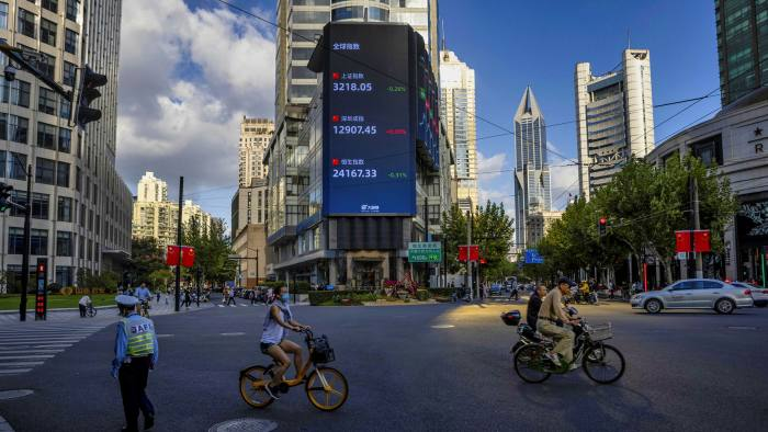 People ride bicycles and scooters on the street beneath a jumbo screen showing the latest stock and currency exchange data in Shanghai. Private enterprises have played the leading role in China's economic transformation but it is no longer possible for trade partners to assume these companies are free agents