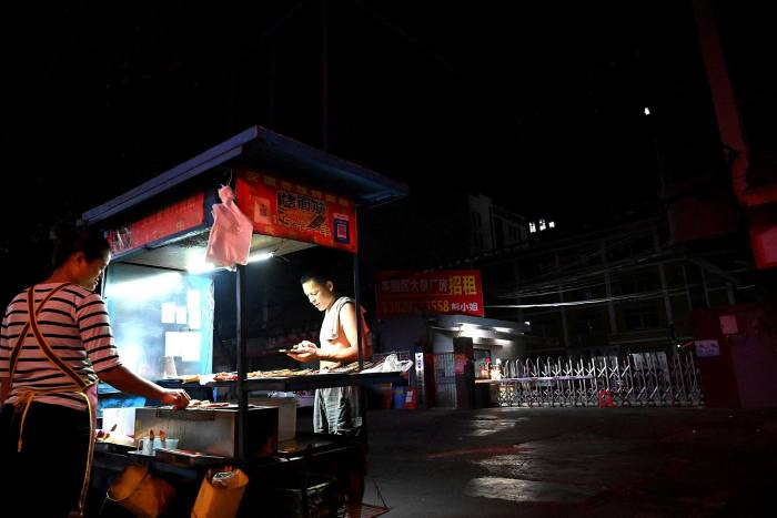 A barbecue stand provides lighting at an industrial park in Houjie, Guangdong province