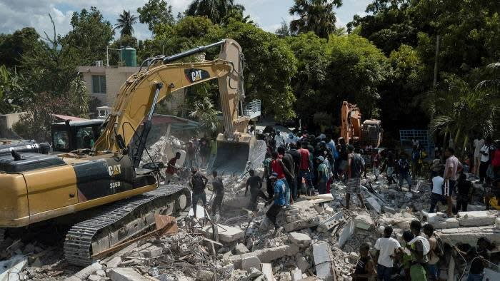 A bulldozer removes debris at the site of at a collapsed hotel in Haiti two days after an earthquake struck the country