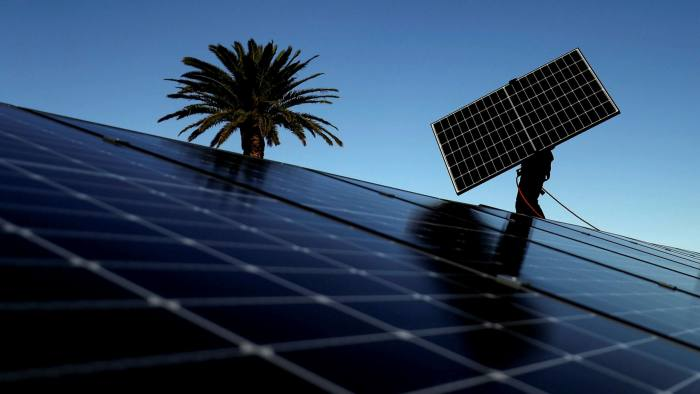 A worker installs solar panels onto the rooftop of a residential property