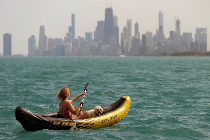 A woman paddles a kayak in Lake Michigan with the Chicago skyline in the background