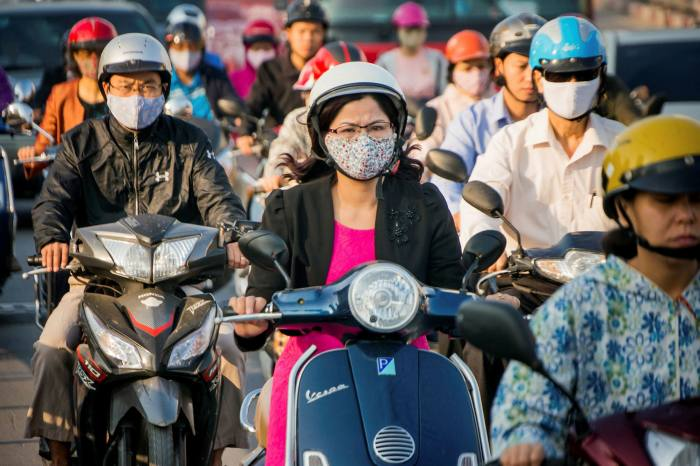 Motorists covered with face masks try to get through the morning's rush hour traffic at the Nga Tu So intersection in Hanoi, Vietnam.