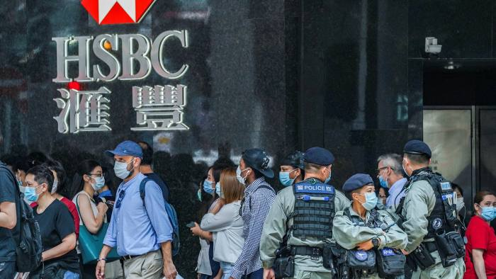Riot police stand guard in Hong Kong's central business district in May. Senior members of the city's government are said to be finding it increasingly difficult to bank with foreign institutions
