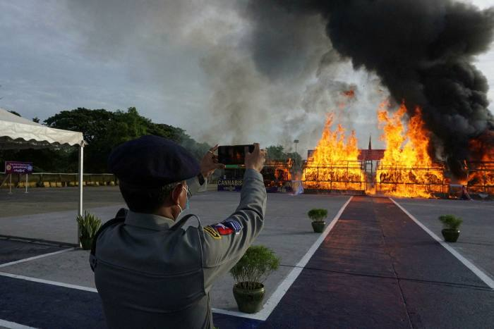 An officer holds up a phone to record a pile of seized illegal drugs being burned in Yangon in June this year
