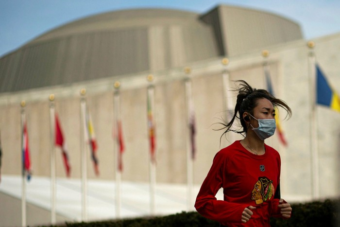 A New York resident wears a face mask as she runs past the UN headquarters