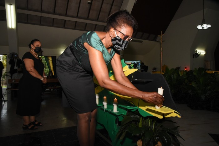 Marcia Bennett, custos rotulorum of St Thomas parish, lights a candle in honour of Jamaican lives lost due to the pandemic at St Theresa Roman Catholic Church in Vineyard Town, St Andrew parish
