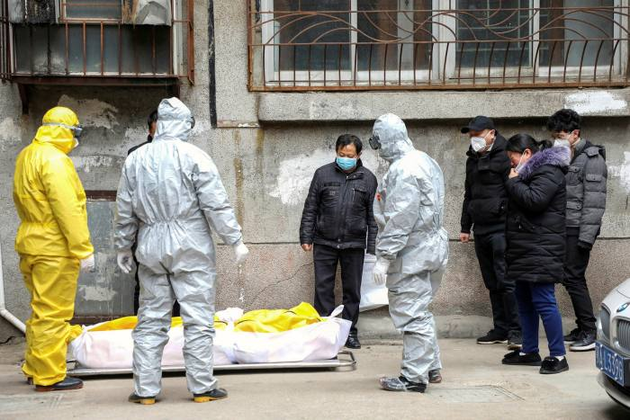 Funeral home workers remove the body of someone suspected to have died from coronavirus at the height of the outbreak in Wuhan