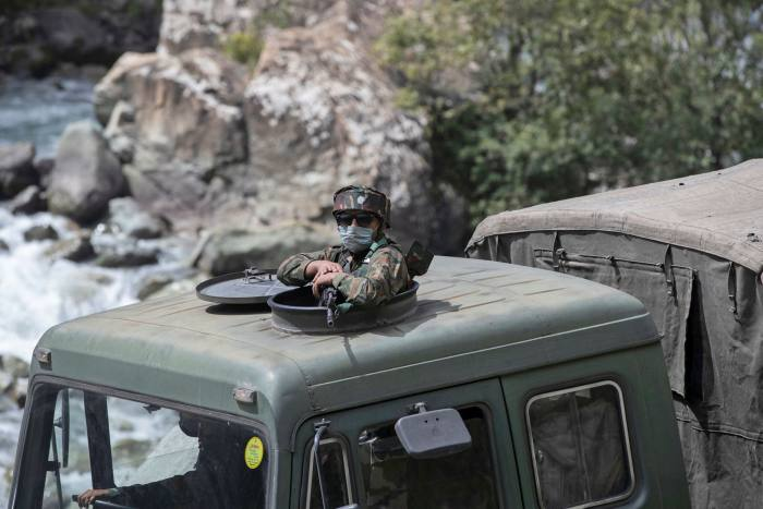 An Indian army soldier keeps guard on top of his vehicle as their convoy moves on the Srinagar-Ladakh highway at Gagangeer, northeast of Srinagar, Indian-controlled Kashmir