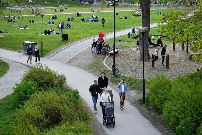 People stroll in Ralambshovsparken park in central Stockholm
