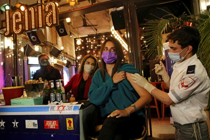 A woman receives a Covid jab in a bar in Tel Aviv. Some leisure activities in Israel will be restricted to those who can prove — using a barcode on an app — that they have either received both doses of a vaccine, or have recovered recently from coronavirus