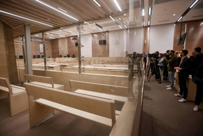 Journalists capture images inside the temporary courtroom prepared for trial over the 2015 terrorist attacks
