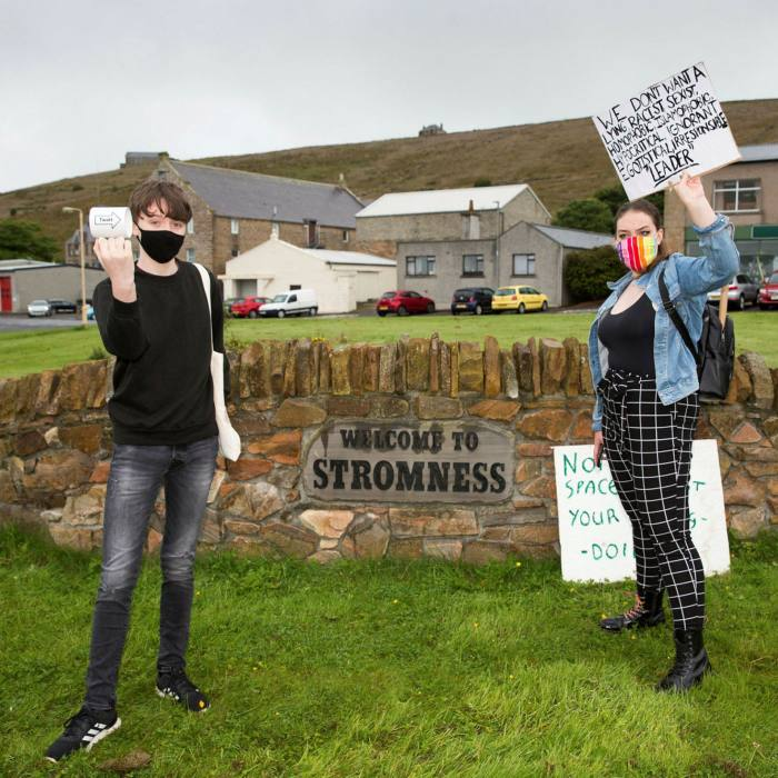 Demonstrators gather to greet Boris Johnson as the prime minister visits the Orkney Islands in July