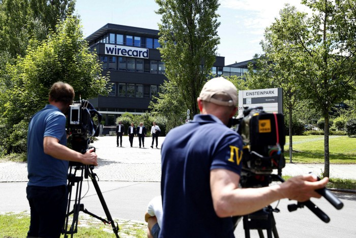 TV news crews film as visitors exit the Wirecard headquarters during a raid by police and prosecutors in Munich last July