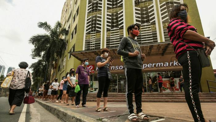 Shoppers in Manila maintain social distance while queuing