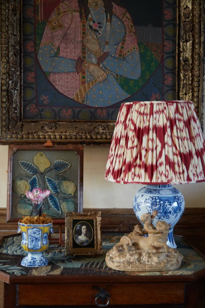 A Delft lamp from Robert Kime, a 17th-century needlework panel of lemons bought at Bonhams, and a portrait miniature by Casper Netscher found at a Brussels antique fair