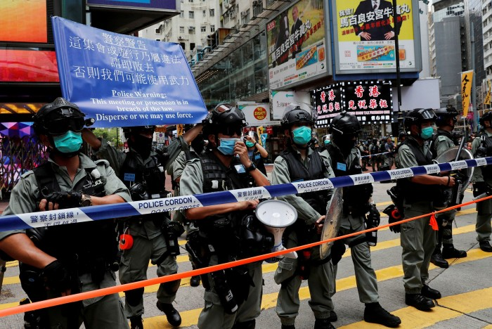 Riot police stand in line as anti-national security law protesters march on the anniversary in July 2020 of Hong Kong's handover to China from Britain