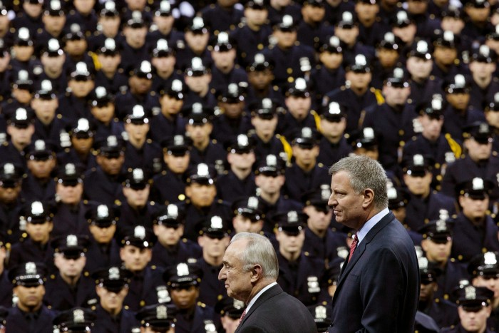 New York City Mayor Bill de Blasio, right, and NYPD commissioner William Bratton at a police graduation ceremony. Mr Bratton introduced the 'broken windows' policing approach, while Mr de Blasio made opposition to 'stop-and-frisk' a centrepiece of his campaign in 2013
