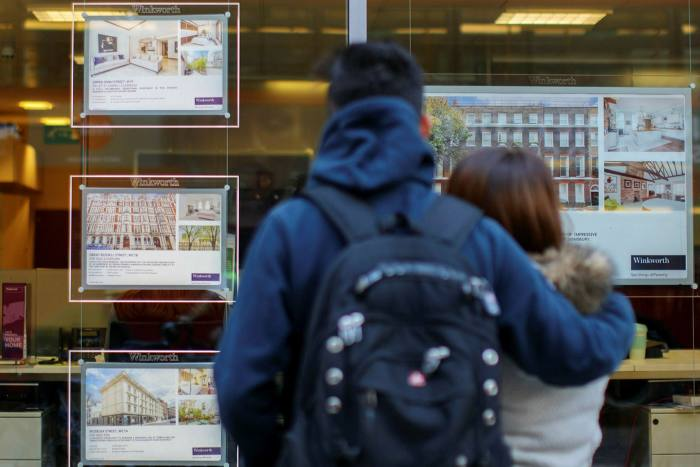 Home buyers look at housing adverts in the window of an estate agent in central London