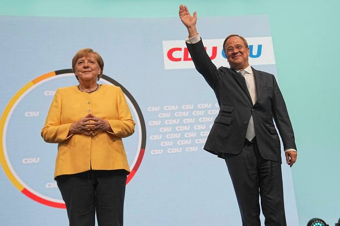 German Chancellor Angela Merkel (L) and Armin Laschet, Minister-President of North Rhine-Westphalia, leader of the Christian Democratic Union (CDU) and candidate for Chancellor, stand on stage at the kick-off of the CDU/CSU's central election campaign at the Tempodrom Berlin