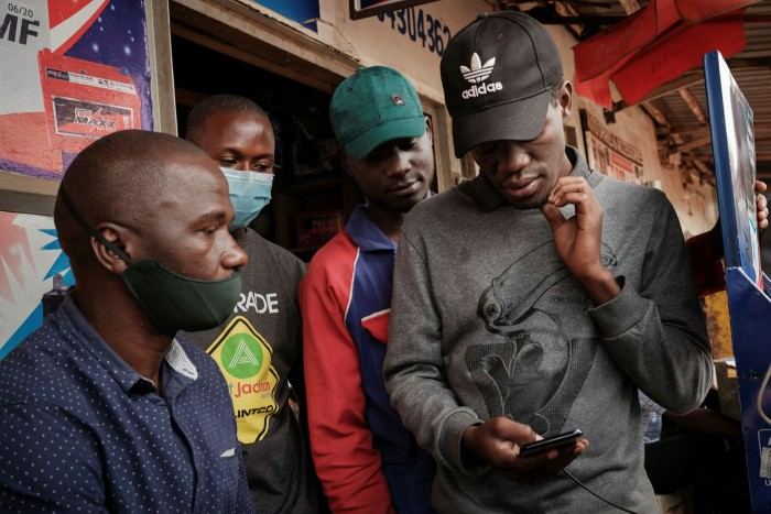 A man browses Facebook on his phone in Kampala, Uganda, Social media platforms were blocked for much of last year's election campaign in the country