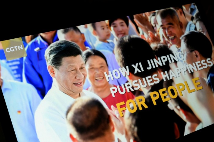 A screen shows a CGTN programme titled 'How Xi Jinping Pursues Happiness for People'