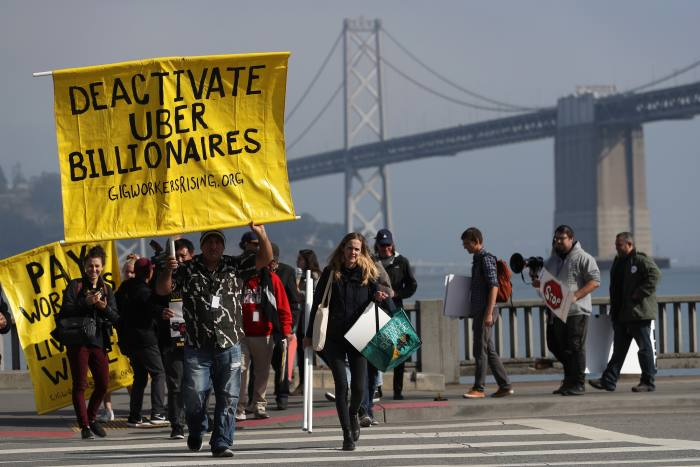 Uber drivers – seen here demonstrating for higher pay in San Francisco last year – are classified as freelance contractors by the company and as such are responsible for fuel and vehicle-maintenance costs