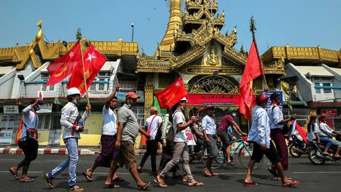 A group of protesters march in Yangon on Monday © Reuters