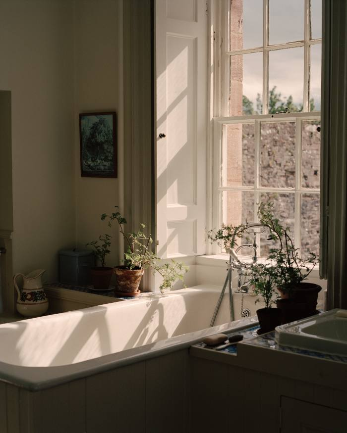 The bath in the open-plan master bedroom, edged with pelargoniums