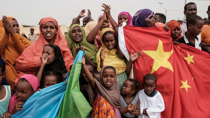 People wave Chinese and Djiboutian national flags