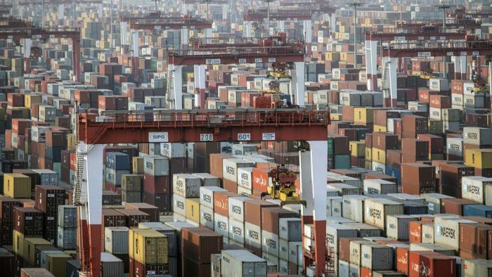 Shipping containers next to gantry cranes in Shanghai, China
