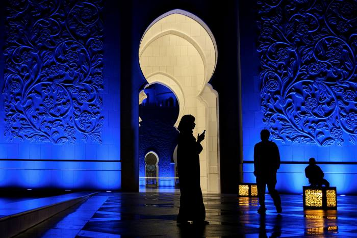 A woman looks at her phone in Sheikh Zayed Grand Mosque in Abu Dhabi. The UAE authorities have been accused of using surveillance to monitor domestic critics and opponents