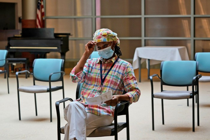 A Certified Nursing Assistant Waits to Receive Her Covid-19 Booster Shot in New York