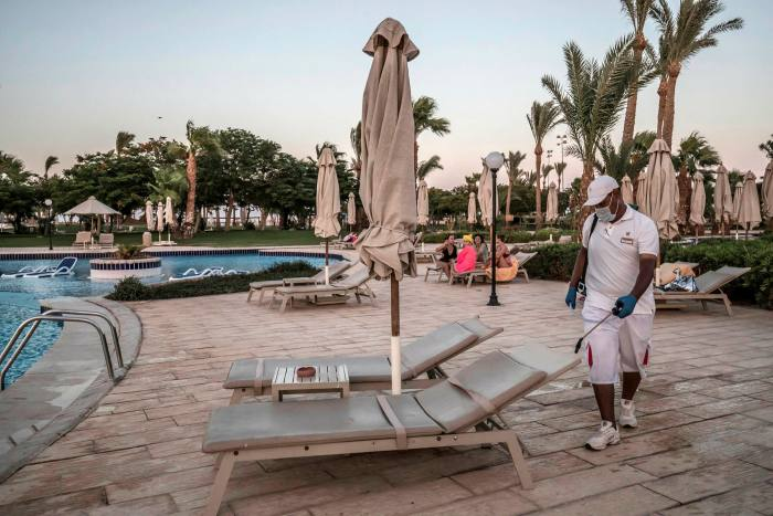 A hotel worker disinfects a beach lounger in Hurghada. The pandemic shuttered Egypt's vital tourism sector as investors pulled at least $13bn from its debt and equity markets