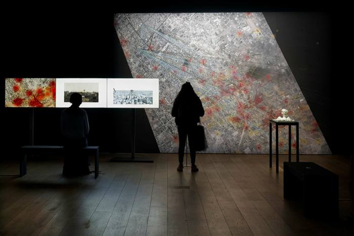 Two people, in silhouette, looking at maps and exhibitions