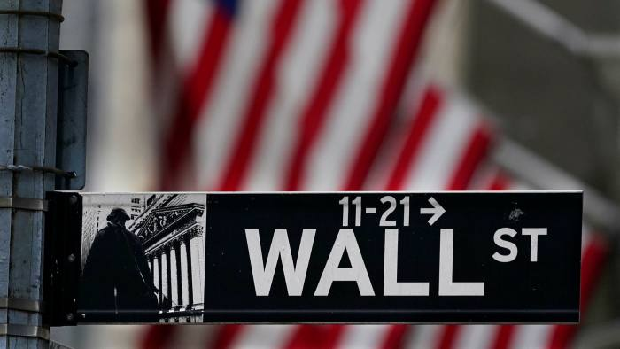 Wall Street sign and a US flag