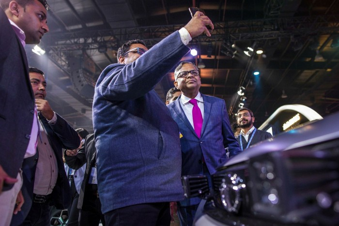 Natarajan Chandrasekaran, Tata Sons chairman, centre-right, poses for a selfie with an attendee at a Tata Motors news conference at the Auto Expo 2020 in Noida, Uttar Pradesh, India, in February