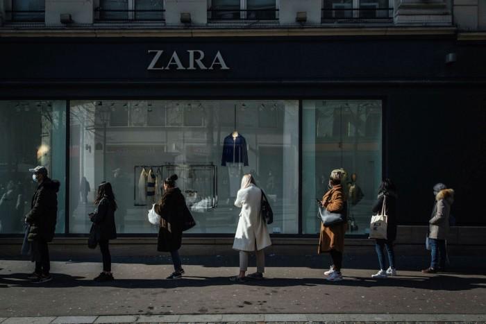 People queue outside a Zara shop window