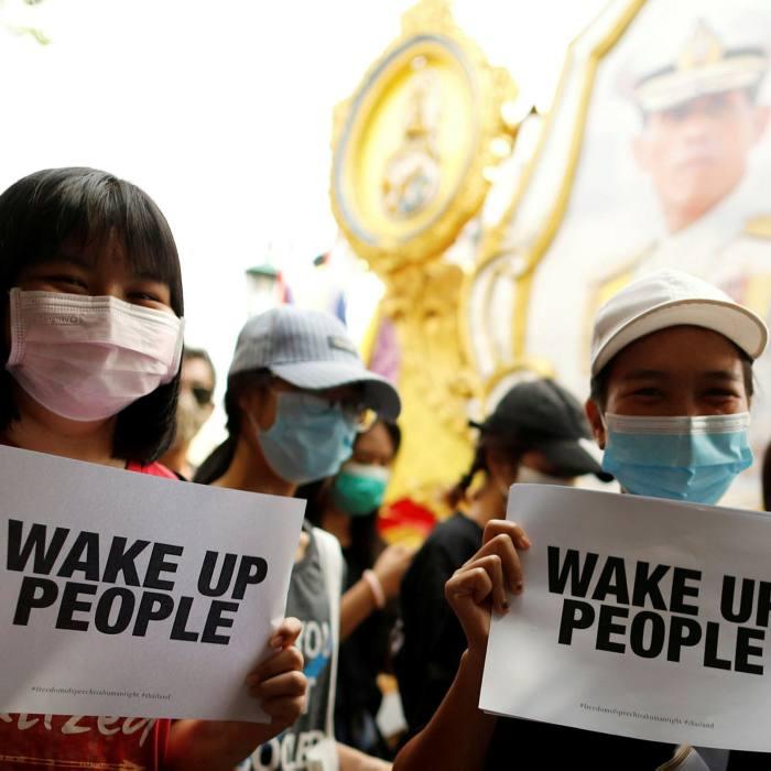 Protesters walk past a picture of King Maha Vajiralongkorn during a rally to demand the resignation of the government