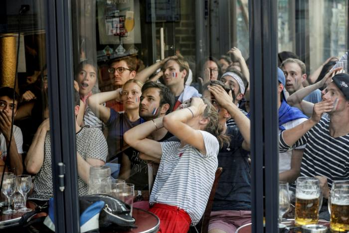 People react as they watch the Russia 2018 World Cup final football match between France and Croatia