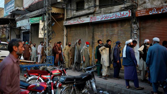 Pakistani labourers queue for free food during a government-imposed coronavirus lockdown this year
