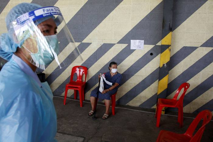 A woman awaits her Covid-19 vaccination at an old warehouse in Bangkok, Thailand, on May 10 2021