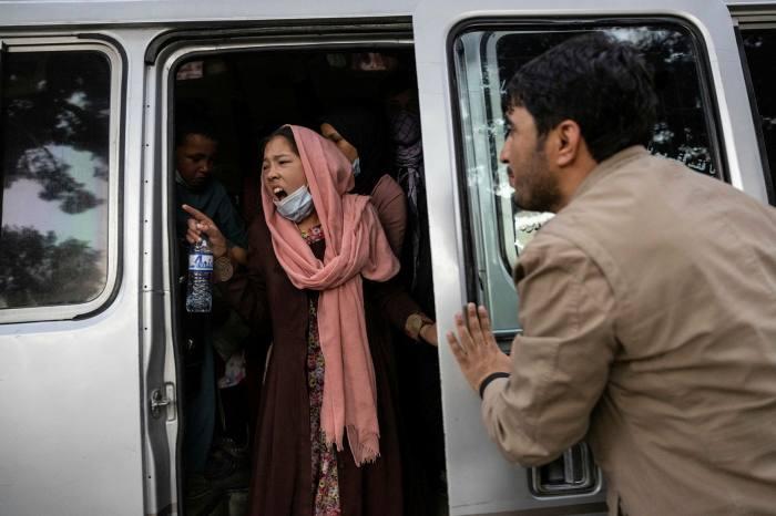 Une femme crie à sa famille de se dépêcher alors que les Afghans déplacés des provinces du nord sont évacués vers diverses mosquées et écoles