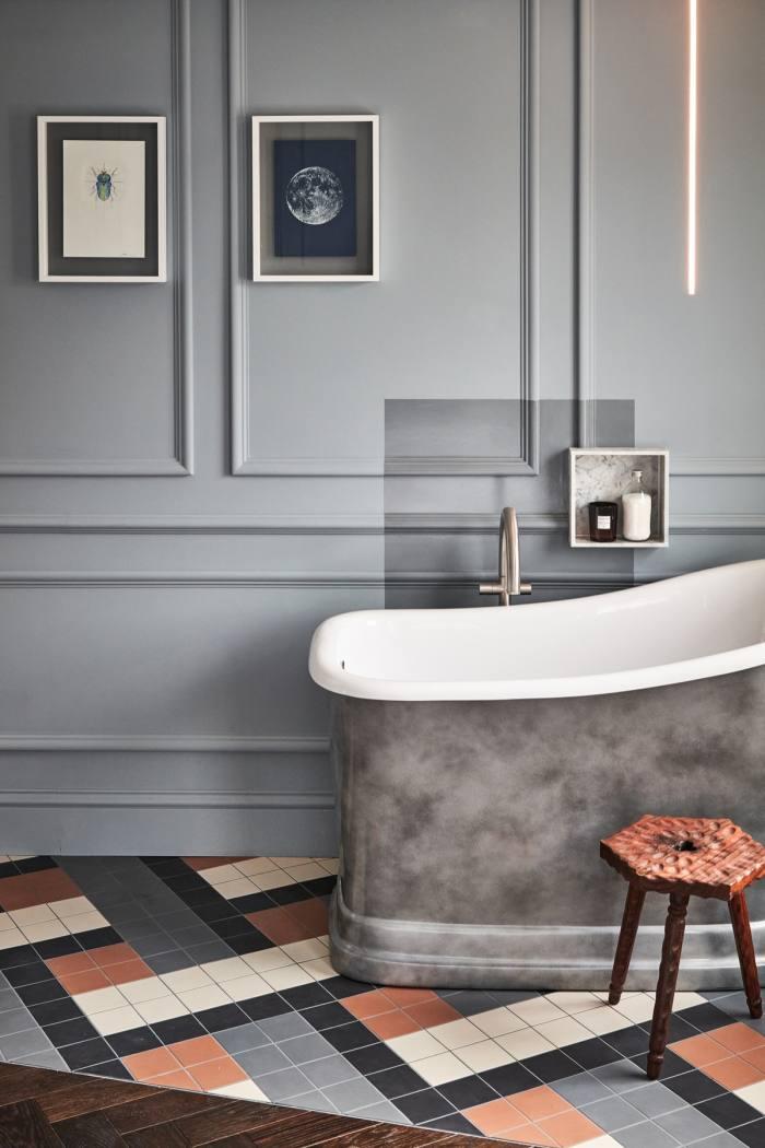 A bathroom with a slipper bath and a geometric-tiled floor
