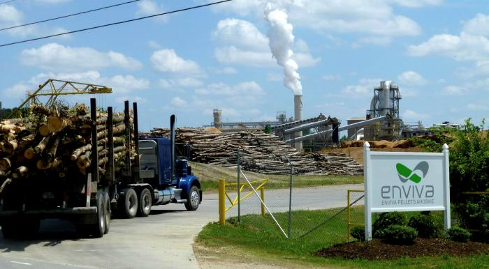 A truck carrying freshly cut timber drives through the entrance to a wood-pellet plant in Ahoskie, North Carolina, with smoking chimneys in the distance