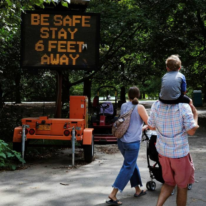 A park sign instructs people to keep their distance in Brooklyn, New York