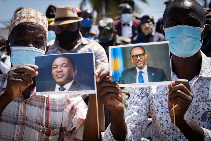 Pemba residents show photos of Mozambican and Rwandan presidents after Paul Kagame arrived to inspect troops