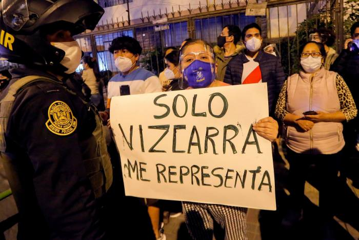 A protester in Lima on Monday holds a sign that reads in Spanish 'Only Vizcarra represents me'