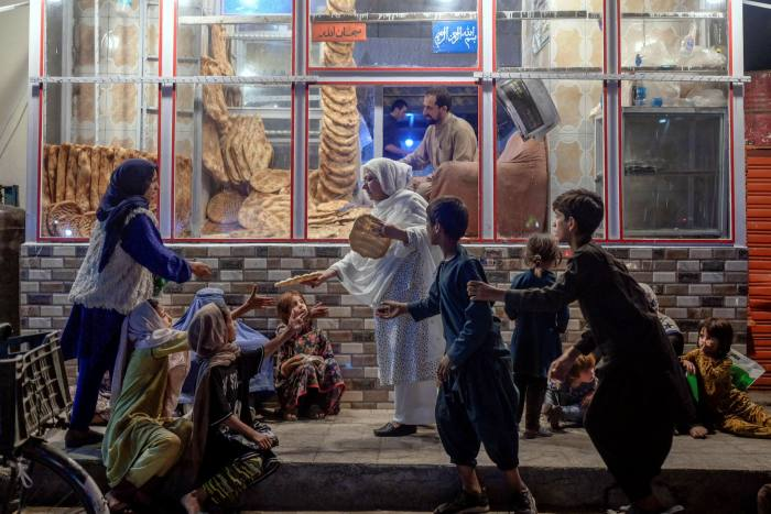 A woman delivers bread to needy youths in front of a bakery in Kabul