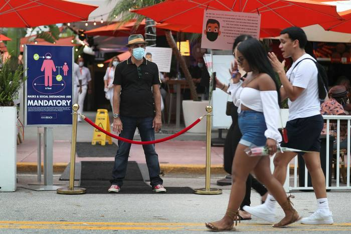 A restaurant host prepares to turn customers away after Miami Beach reintroduced an 8pm-6am curfew to fight the spread of coronavirus